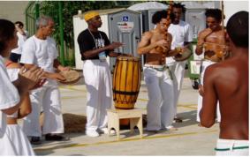 Mestre Alcides toca atabaque e canta na apresentação do Maculelê.
